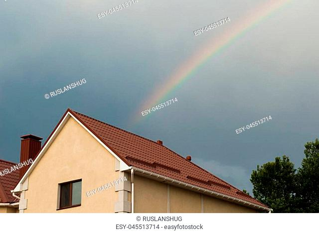 roof of private house against sky and rainbow