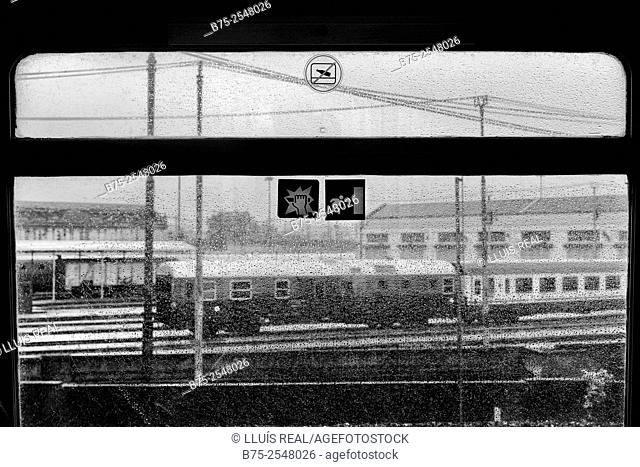 View from the window of a train on a rainy day of the platforms of a train station of Milan, with rail tracks, poles with electrical wires and two vagons