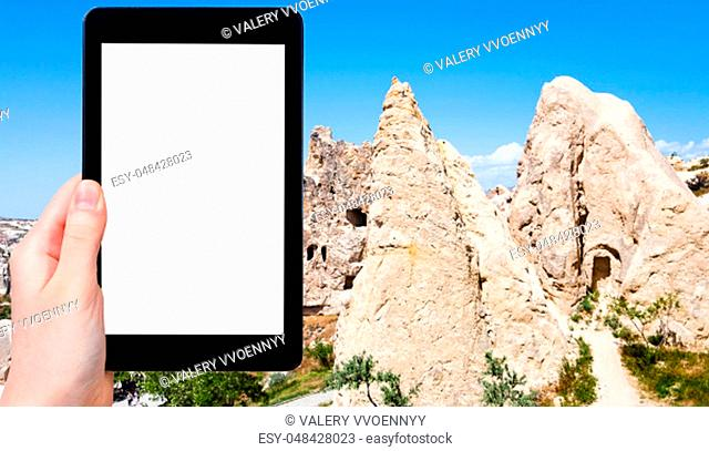 travel concept - tourist photographs of ancient cave monastic settlement near Goreme town in Cappadocia in spring in Turkey on smartphone with empty cutout...