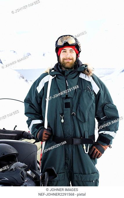 Portrait of young man standing next to snowmobile