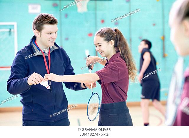 Gym teacher teaching high school student badminton in gym