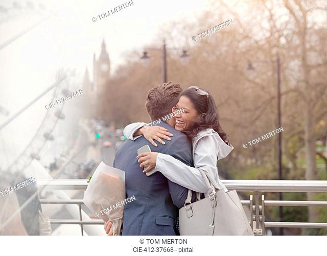 Smiling couple hugging, boyfriend surprising girlfriend with flowers on urban bridge, London, UK