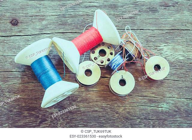 thread rolls on wood background with filter effect retro vintage style