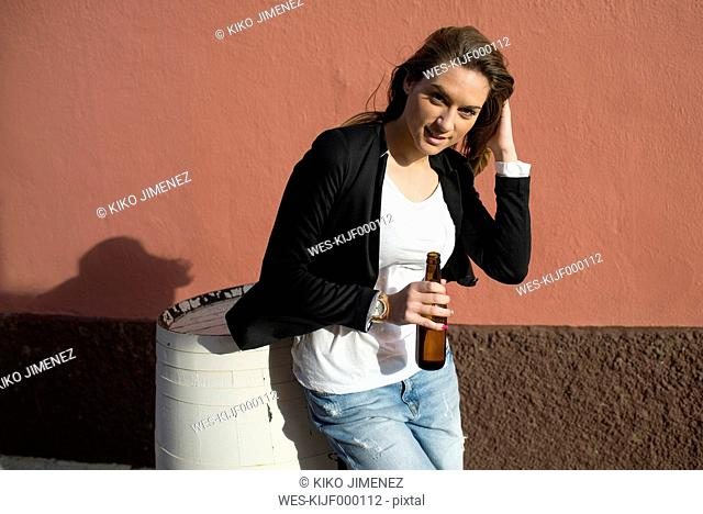Portrait of woman holding bottle of beer