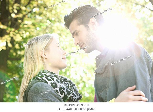 Couple standing together outdoors, looking into each other's eyes