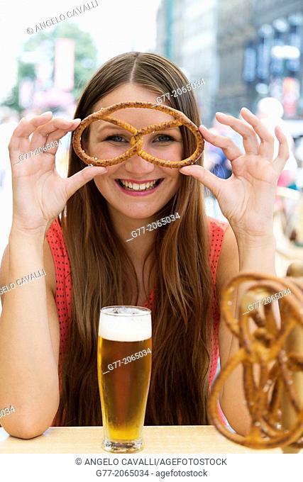 Czech Republic. Prague. Young smiling woman watching through a Pretzel