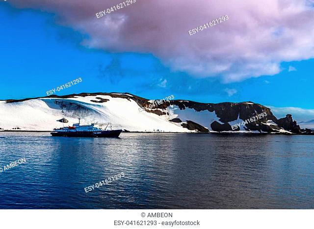 Cruise ship standing still on the sea surface with snow covered mountains in the background, close to Half Moon island, Antarctic