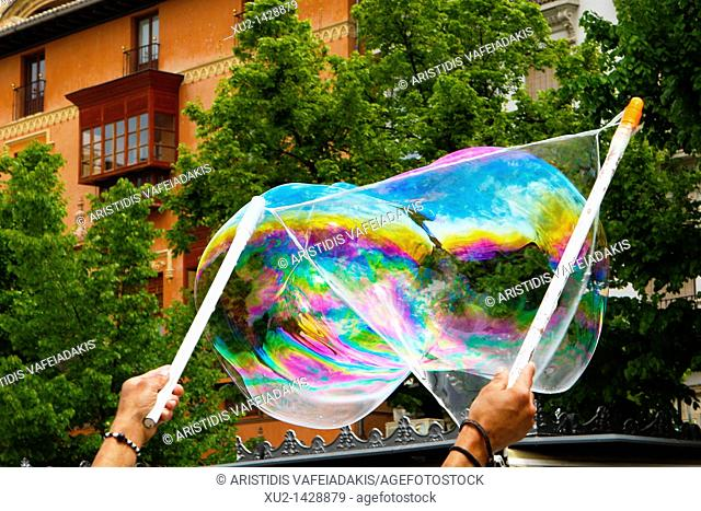 Street artist make a shoap bubble for the children at plaza Bib-Rambla in Granada Spain