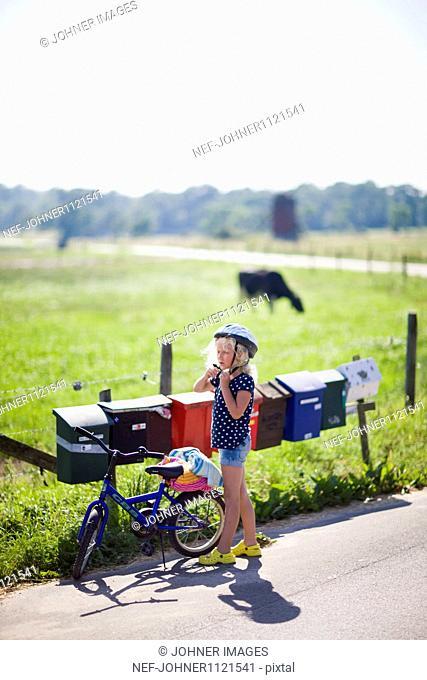 Girl wearing cycling helmet standing on road