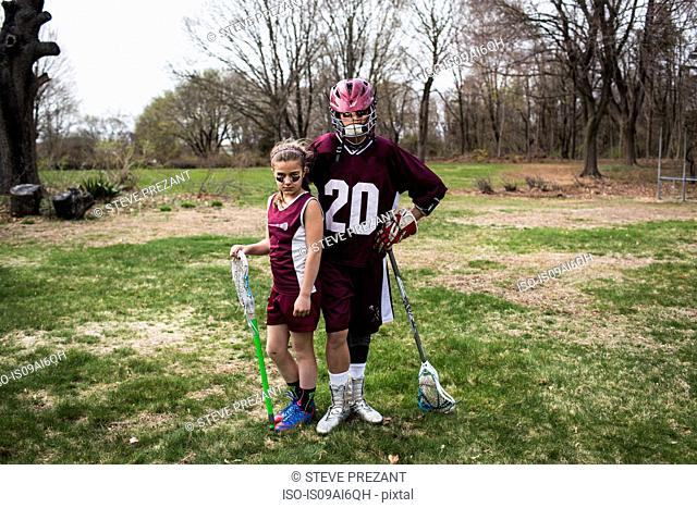 Brother and sister wearing lacrosse uniforms