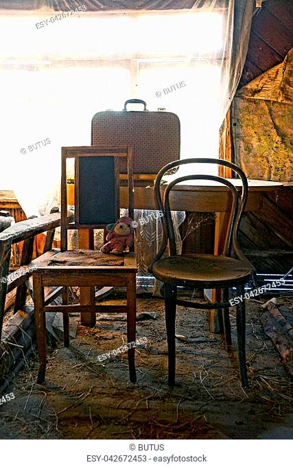 old wooden brown chairs and a suitcase on a table by the window with a curtain in the room