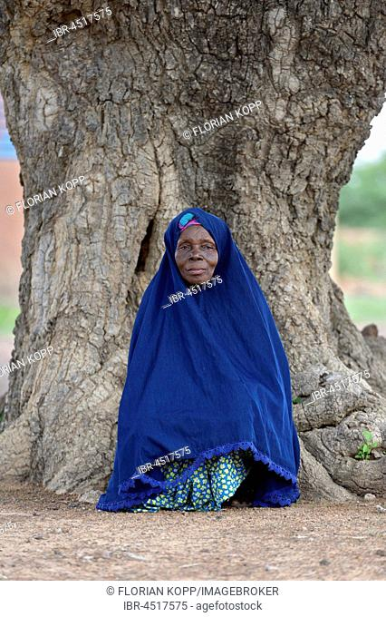 Old woman leaning against the trunk of an old tree, portrait, village Toeghin, Oubritenga province, Plateau Central region, Burkina Faso