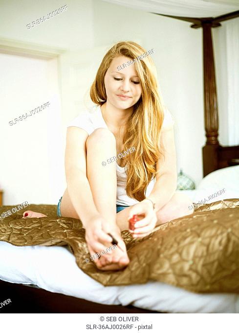 Teenage girl painting her toenails