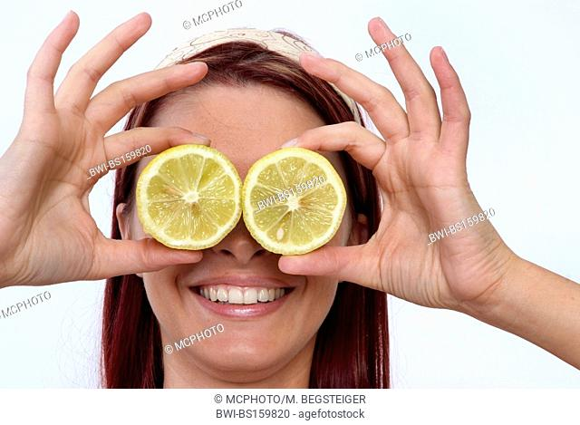 woman holds citron slices in front of her eyes
