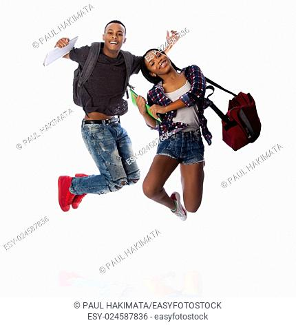 Two happy students jumping of happiness celebrating, carrying notepads and bags, on white