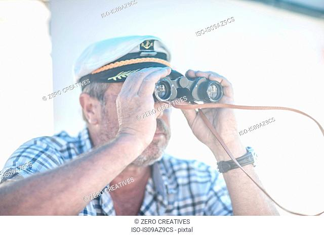 Boat captain looking through binoculars on boat, Cape Town, South Africa