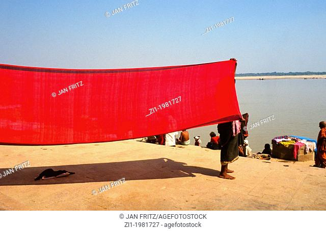 woman dries her red sari in the wind at the border of the Ganges in Varanasi, India