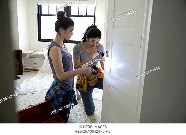Mother and teenage daughter fixing door handle
