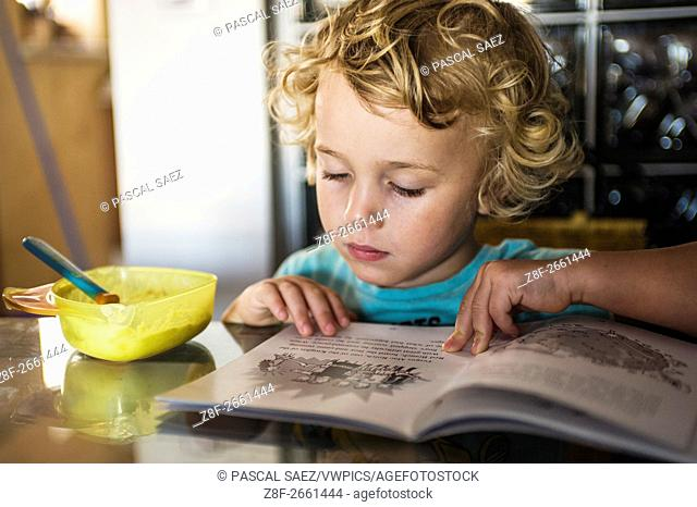 A little boy (age 3-and-a-half years) reads a book at a table in his home