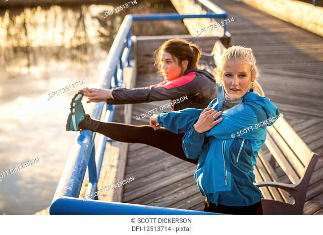 Two young women stretching on a trail at the water's edge; Anchorage, Alaska, United States of America