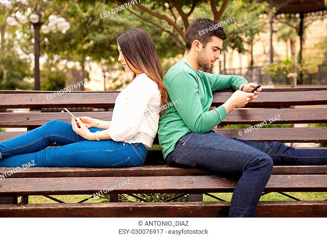 Profile view of a young couple sitting back to back and using their smartphones while ignoring each other
