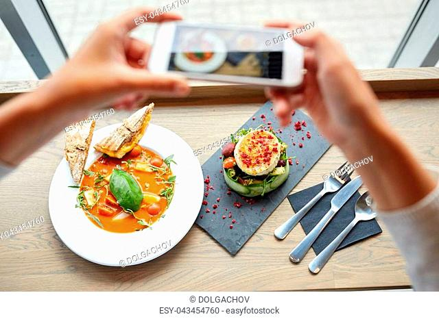 food, eating, technology, culinary and people concept - woman hands with smartphone photographing gazpacho soup and salad at restaurant