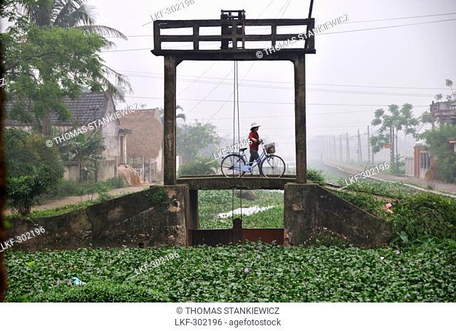 Person pushing bike, landscape in Halong bay near Ninh Binh, north Vietnam, Vietnam