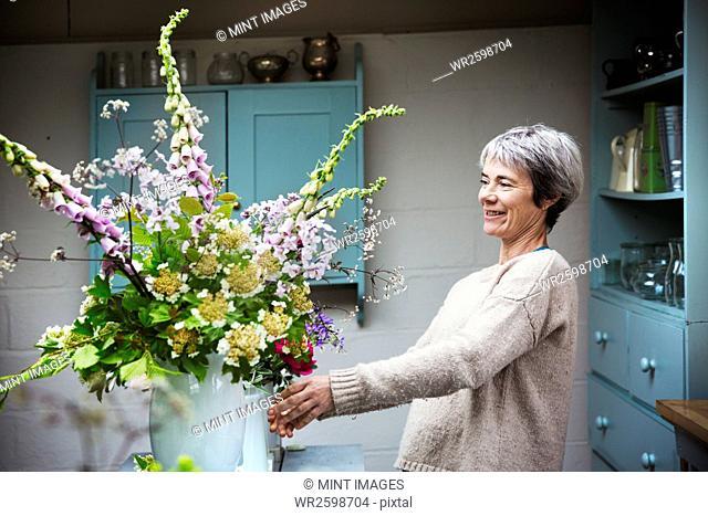 A florist working on a tall vase arrangement of flowers