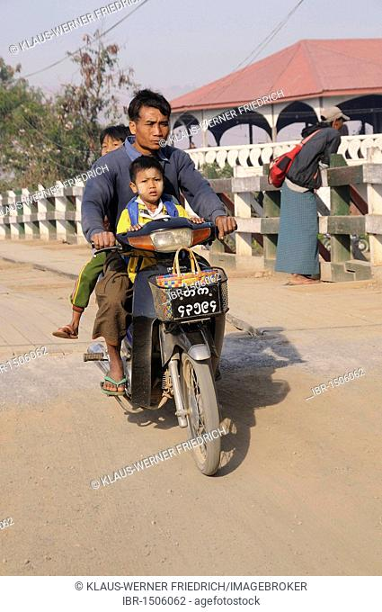 Motorcyclist carrying two boys, one having Tanaka paste on his face, riding across a bridge in Nyaungshwe, Inle Lake, Myanmar, Burma, Southeast Asia, Asia