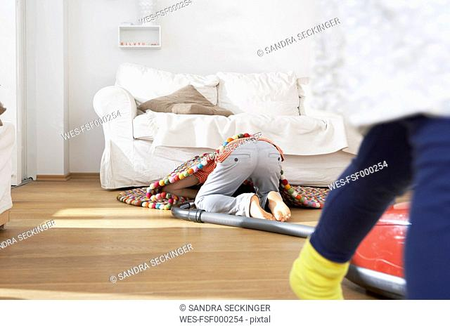 Boy in living room hoovering under carpet