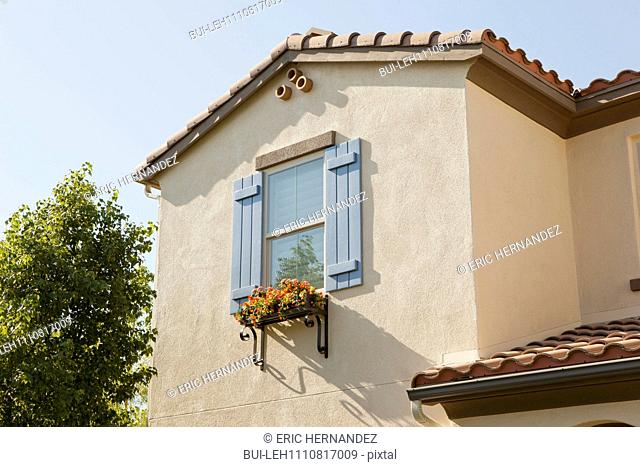 Low angle view of a window with flower box on house wall against clear sky