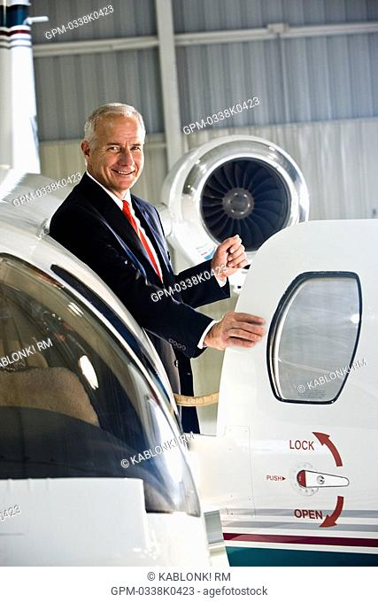 Businessman standing at doorway of corporate jet