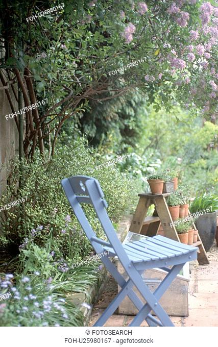 Blue wooden chair below purple lilac in country garden