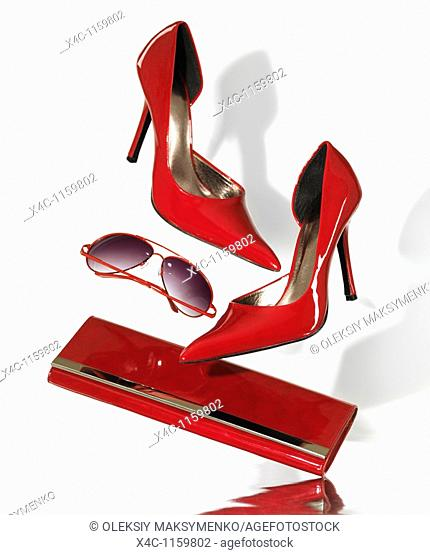 Stylish red high heel stiletto shoes sunglasses and a clutch hand bag falling on metal surface isolated on white background