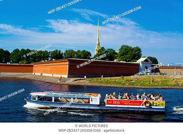 Sightseeing cruise tour boat on Neva river, with Peter and Paul fortress in background, Saint Petersburg, Russia, Europe