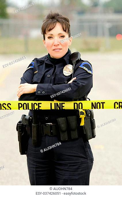 a Hispanic police officer standing behind yellow crime scene tape