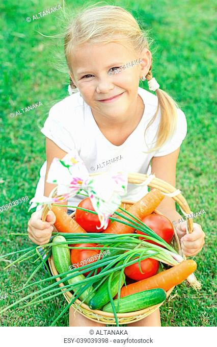 Happy little girl sitting on the grass with a basket of vegetables at the day time. Concept of healthy food