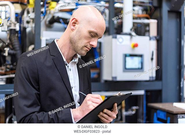 Businessman writing on clipboard in modern factory