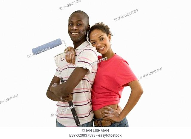 Young couple home decorating, man with paint roller, woman embracing man, smiling, portrait, cut out