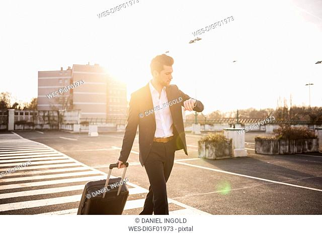 Businessman with rolling suitcase checking the time