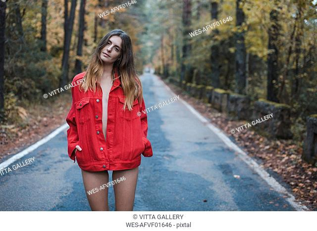 Portrait of young woman standing on country road wearing red jacket
