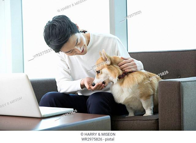 Young smiling bachelor petting his pet dog