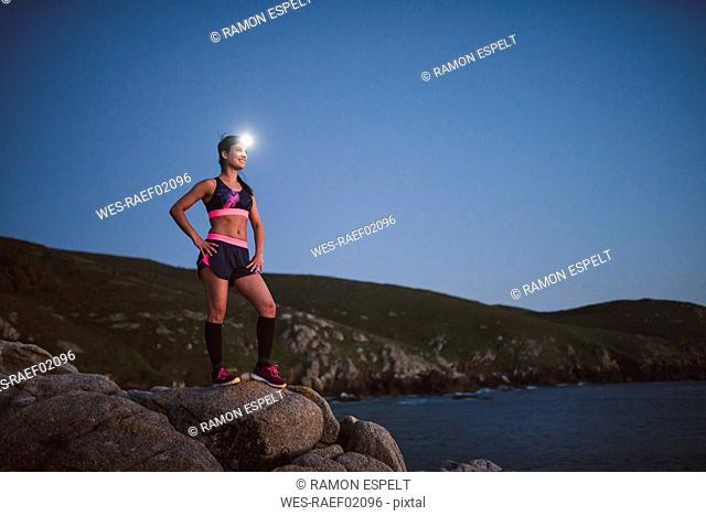 Sportive woman with headlamp standing on rocks in the evening