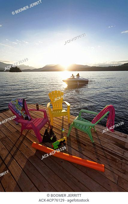 Boaters returning home at the end of the day pass by a dock on Sproat Lake, Sproat Lake, Port Alberni, Vancouver Island, British Columbia, Canada