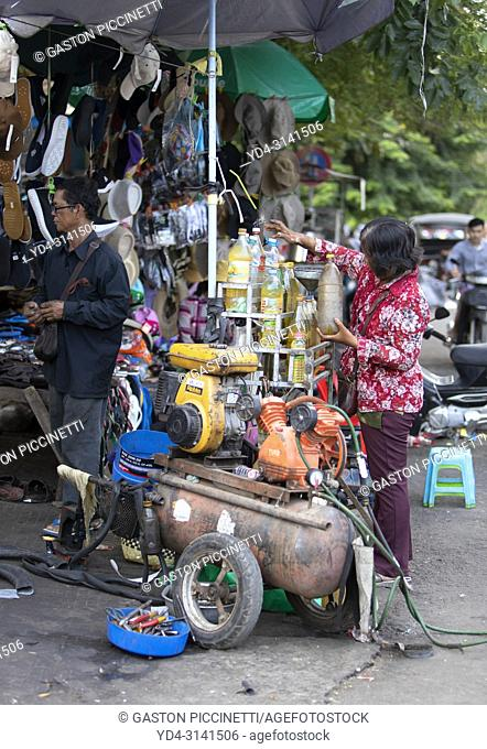 Small street gas station, this is where people buy gas for their motorcycles. The bottles are filled by hand one by one from a main tank and then sold to the...
