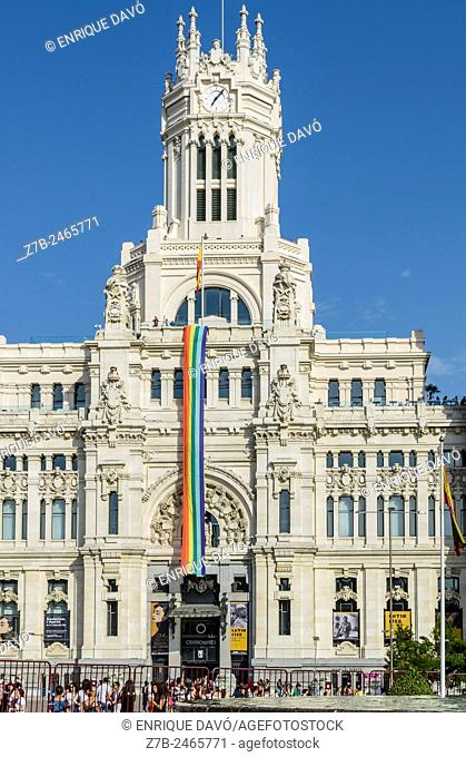 View of Correos palace with rainbow flag in Cibeles square, Madrid city, Spain