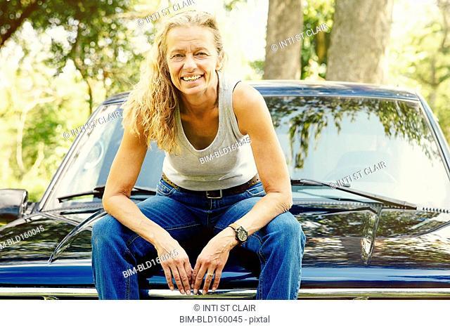 Caucasian woman sitting on car hood