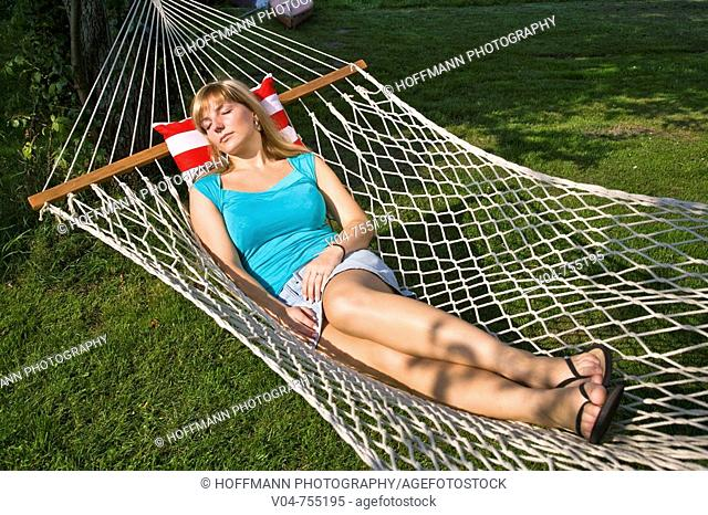 Young woman sleeping in a hammock in the garden