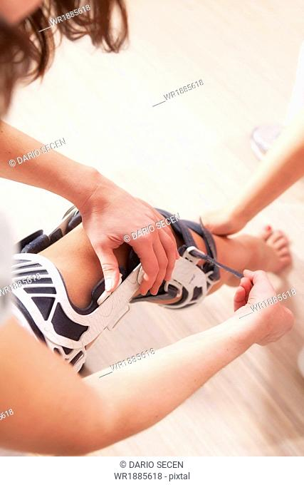 Osteopathy, Patient getting a knee support, Munich, Bavaria, Germany