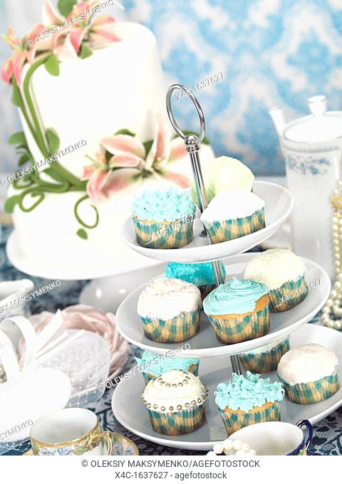 Food still life photo of cupcakes, china and a cake on a table